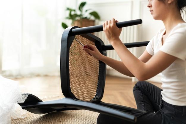 Frau baut einen diy-stuhl von grund auf zusammen