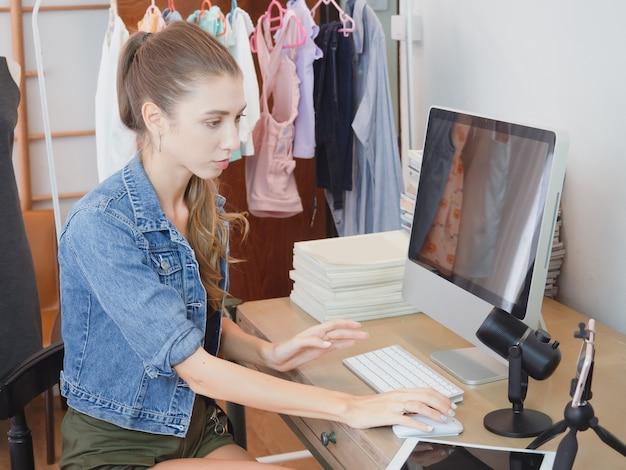 Frau beantworten die fragen der kunden über ihren computer über verkauf online, mädchen, das geschäft in ihrem haus tätigt