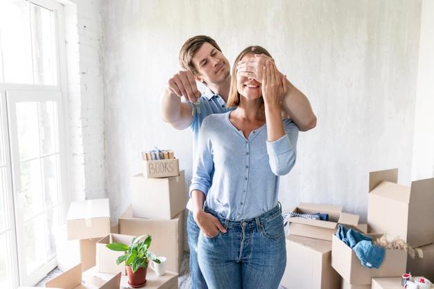 Frau bedeckt ihr gesicht, während partner sie mit schlüsseln für neues zuhause überrascht