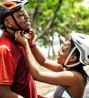 Frau befestigt einen fahrradhelm für ihren freund