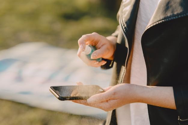 Frau behandelt ihr telefon mit antiseptikum