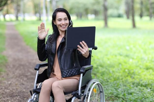 Frau behinderter operator in kopfhörern mit mikrofon und laptop arbeitet im rollstuhl im park