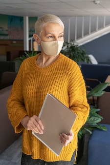 Frau bei der arbeit, die eine medizinische maske trägt