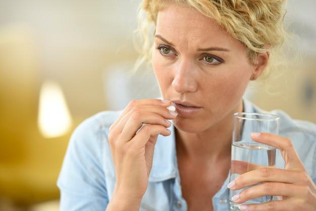 Frau bei der arbeit, die pille nimmt, um kopfschmerzen zu erleichtern