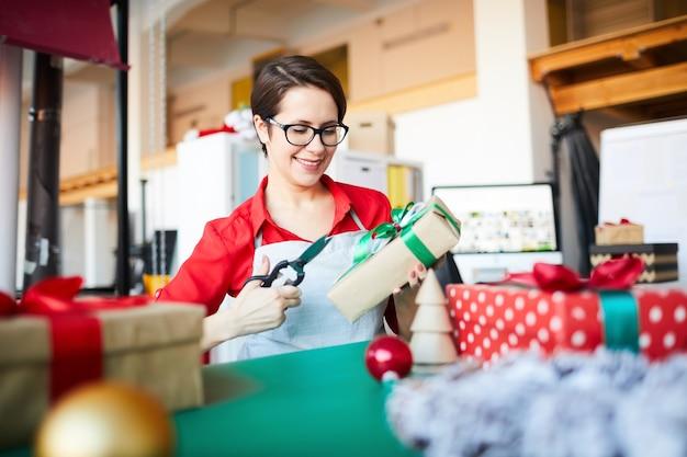 Frau bei der arbeit, einen weihnachtskranz machend und geschenke einpackend