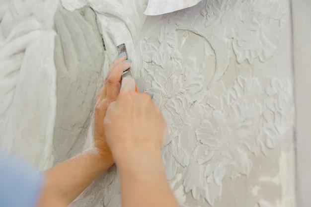 Frau bei der arbeit mit meißelwerkzeug schnitzt flachreliefmuster an der wand