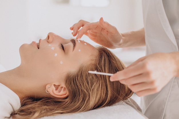 Frau bei kosmetikerin mit schönheitsbehandlung