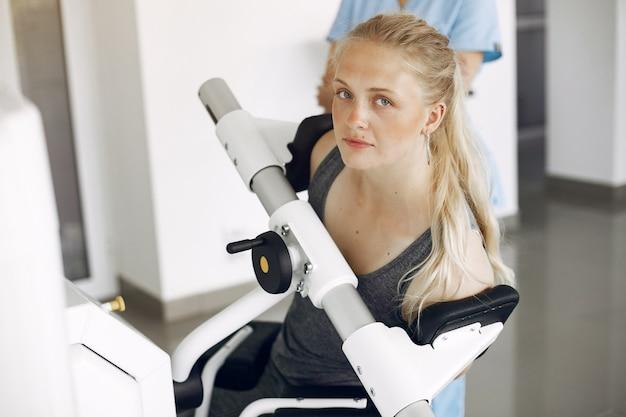 Frau bei physiotherapie, die körperliche übungen mit qualifiziertem therapeuten macht