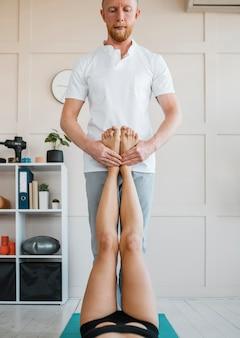 Frau bei physiotherapie mit männlichem physiotherapeuten