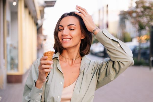 Frau bei sonnenuntergang im sommer mit eistüte in der stadtstraße