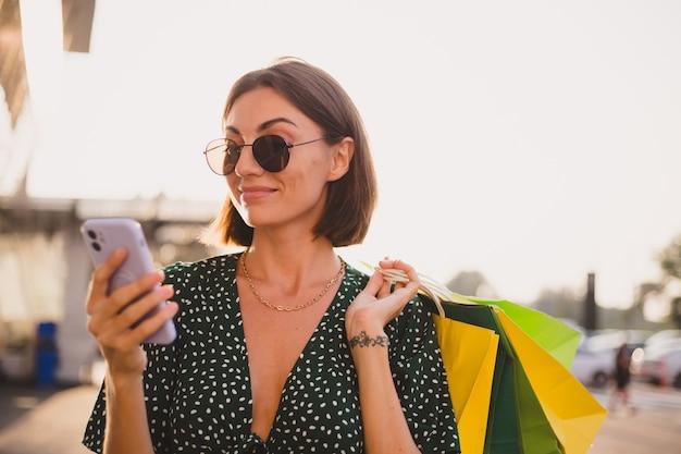 Frau bei sonnenuntergang mit bunten einkaufstüten und parkplatz am einkaufszentrum glücklich mit handy