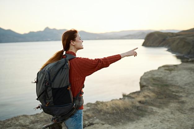 Frau bei sonnenuntergang nahe dem meer in den bergen mit einem rucksack auf ihren schultern