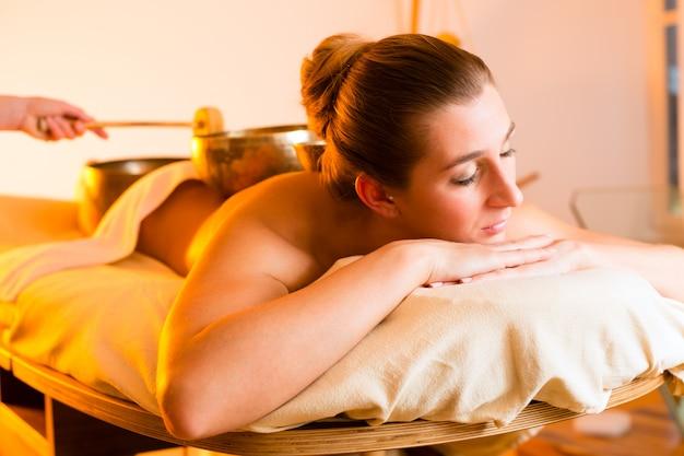 Frau bei wellnessmassage mit klangschalen