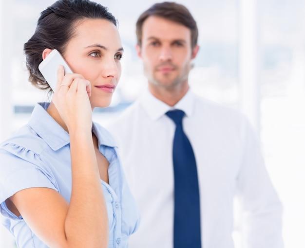 Frau beim anruf mit kollegen im hintergrund im büro