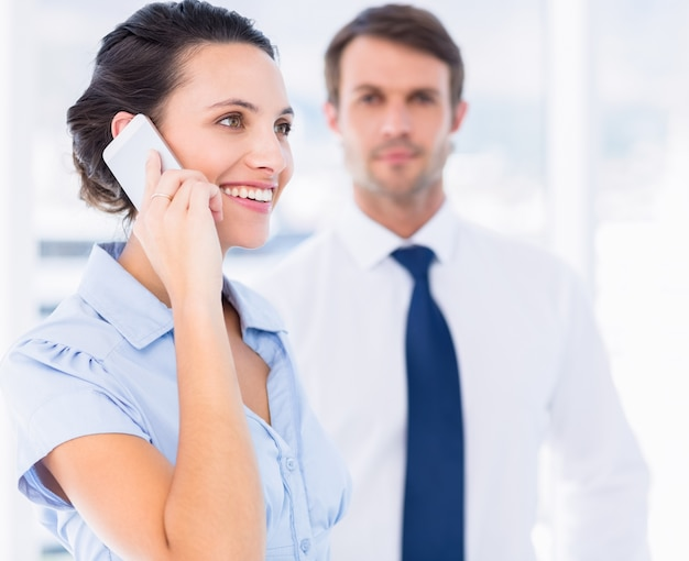 Frau beim anruf mit männlichem kollegen im hintergrund