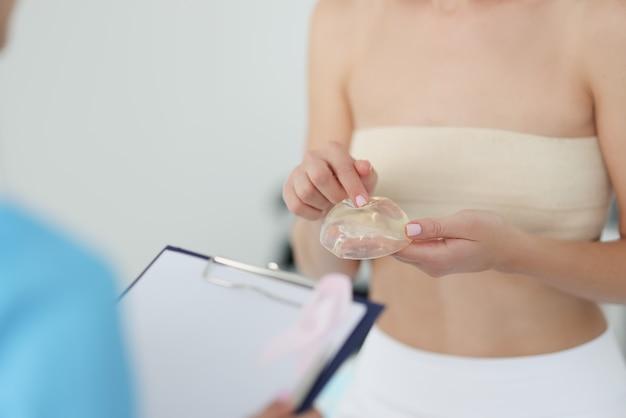 Frau beim arzttermin hält brustsilikonimplantat. konzept der brustvergrößerungsoperation