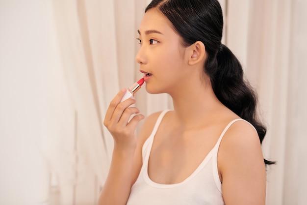 Frau beim auftragen von make-up für ein abendliches date vor einem spiegel. konzentriere dich auf ihr spiegelbild