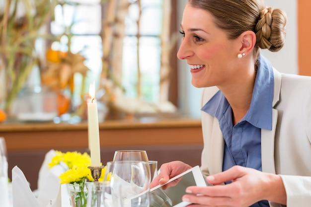 Frau beim business-lunch mit tablet-computer