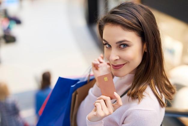 Frau beim einkaufen mit kreditkarte bezahlen
