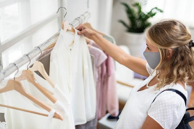 Frau beim einkaufen mit maske die neue normalität