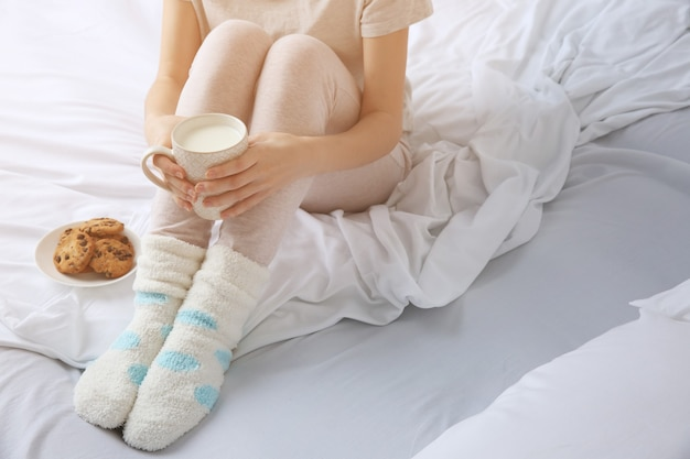 Frau beim frühstück mit keksen und tasse milch auf dem bett, nahaufnahme