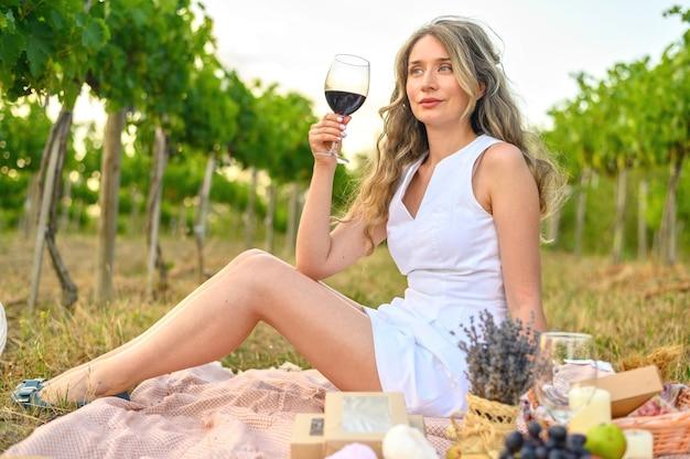 Frau beim picknick mit einem glas wein