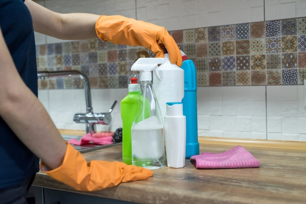 Frau beim reinigen der oberfläche eines küchentischs mit schwamm in ihren gummihandschuhen. hausarbeit