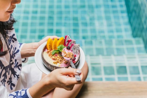 Frau beim smoothie-frühstück am swimmingpool Premium Fotos