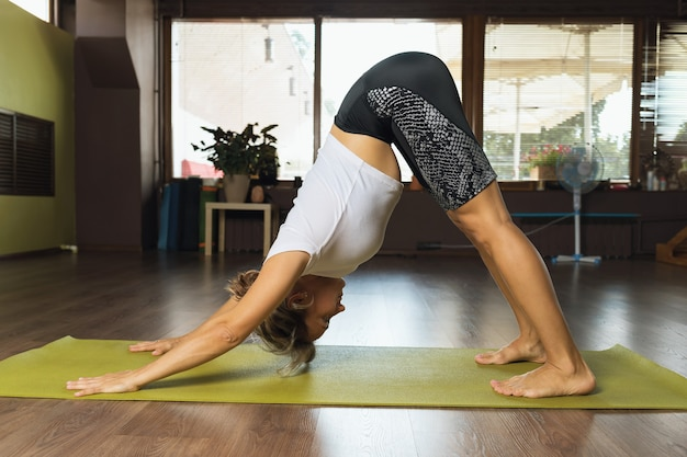 Frau beim yoga führt im studio die übung adho mukha shvanasana . durch