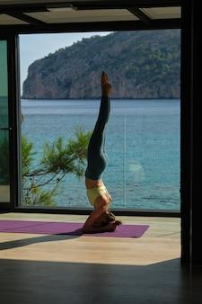 Frau beim yoga in unterstützter kopfstandhaltung