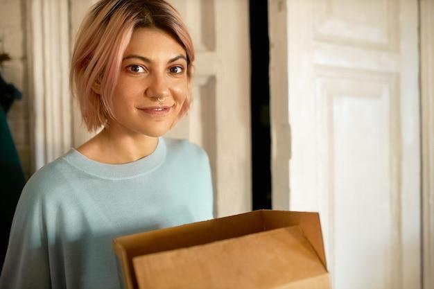 Frau bekommt ein geschenk von der post zu ihrem haus.