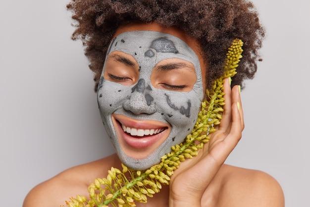 Frau bekommt gesichtsmaske aus natürlichen pflanzlichen inhaltsstoffen lächelt zahnig hält die augen geschlossen steht mit nackten schultern genießt schönheitsprodukt-posen im innenbereich. dermatologische hautpflege