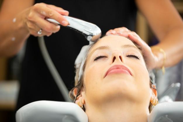 Frau bekommt haare im friseursalon gewaschen