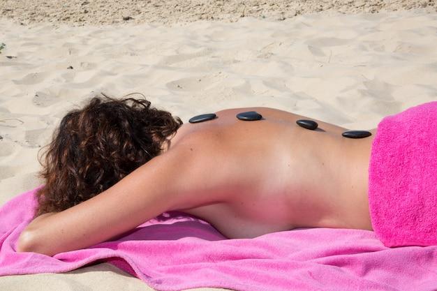 Frau bekommt heiße steine behandlung am strand gemacht