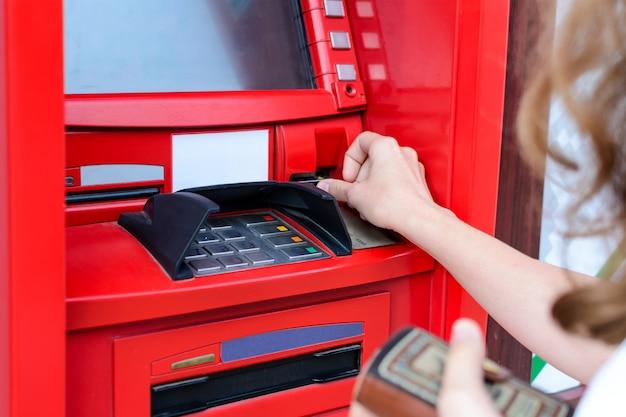 Frau benutzt eine kreditkarte am geldautomaten nahaufnahme