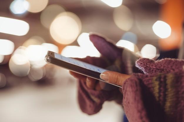 Frau benutzt einen smartphone nachts in der stadt