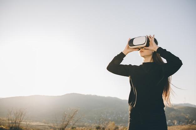 Frau benutzt gläser der virtuellen realität bei sonnenuntergang. abendzeit, dämmerung. entspannen sie sich, unterhaltung und technologiekonzept