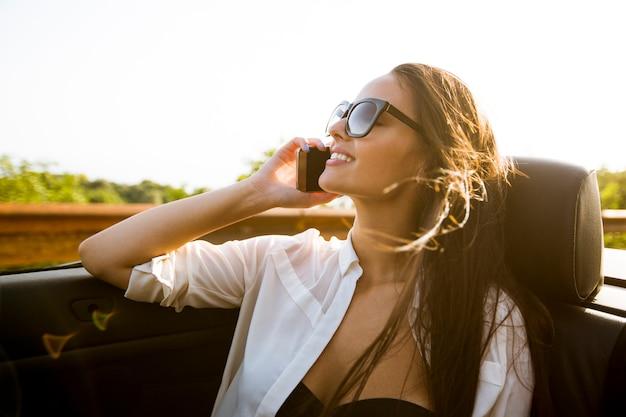 Frau benutzt handy und stationiert im cabriolet am sommertag