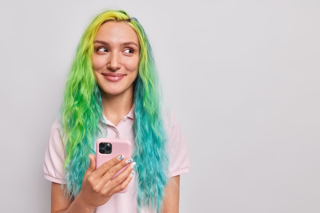 Frau benutzt handy zum online-chatten hat lange gefärbte bunte haare verwendet app-messaging oder shopping lässig gekleidet isoliert auf grau