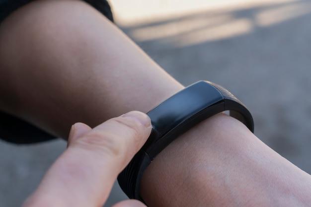 Frau benutzt ihren finger, um die smartwatch einzustellen