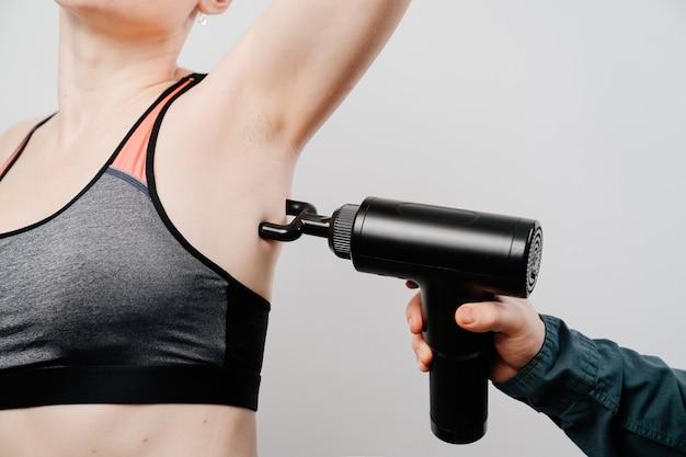 Frau benutzt massagepistole.