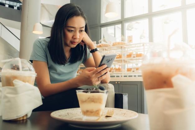 Frau benutzt smartphone im bäckerei-café.