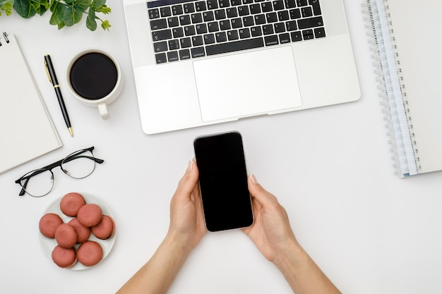 Frau benutzt smartphone mit leerem bildschirm über weißem schreibtisch mit laptop