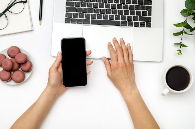 Frau benutzt smartphone mit leerem bildschirm über weißem schreibtisch
