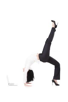 Frau beobachtet den laptop einen handstand brücke tun