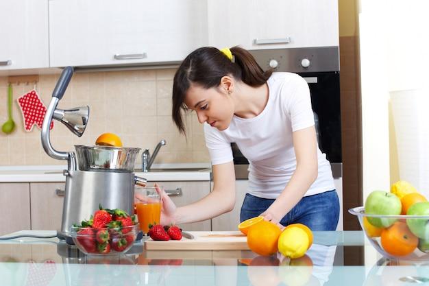 Frau bereiten einen saft der frucht mit quetscher zu
