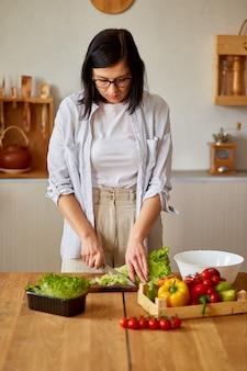 Frau bereitet gemüsesalat in der küche vor