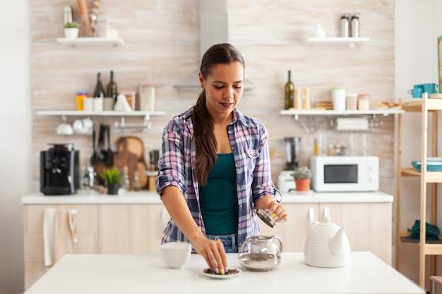 Frau bereitet grünen tee zum frühstück in der küche zu