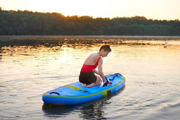 Frau bereitet ihr paddleboard für einen tag am fluss vor