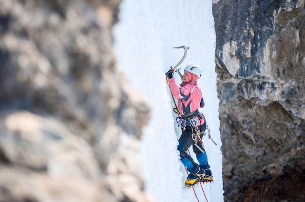 Frau bergsteiger klettern einen gefrorenen wasserfall und lächelnd